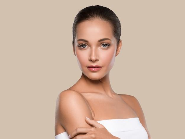 Kobieta piękna twarz zdrowej skóry naturalny makijaż piękny młody model. kolor tła. brązowy
