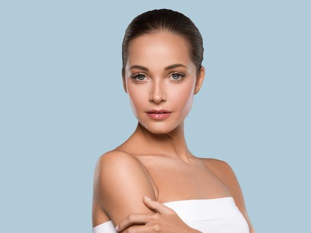 Kobieta piękna twarz zdrowej skóry naturalny makijaż piękny młody model. kolor tła. niebieski