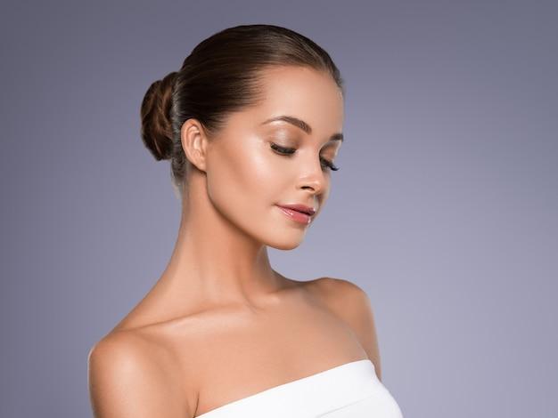 Kobieta piękna twarz zdrowej skóry naturalny makijaż piękny młody model. kolor tła. purpurowy