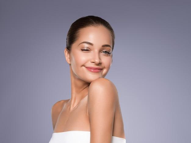 Kobieta piękna twarz zdrowej skóry naturalny makijaż piękny młody model. kolor tła. szary