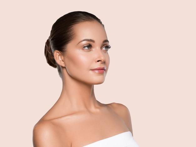 Kobieta piękna twarz zdrowej skóry naturalny makijaż piękny młody model. kolor tła. żółty