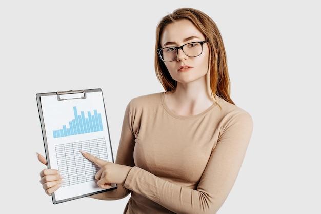 Kobieta piękny młody biznes w okularach na białym tle na szarym tle. osiągnięcie koncepcji biznesowej bogactwa kariery. miejsce na kopię makiety. trzymaj schowek z dokumentami, wykresami i raportami