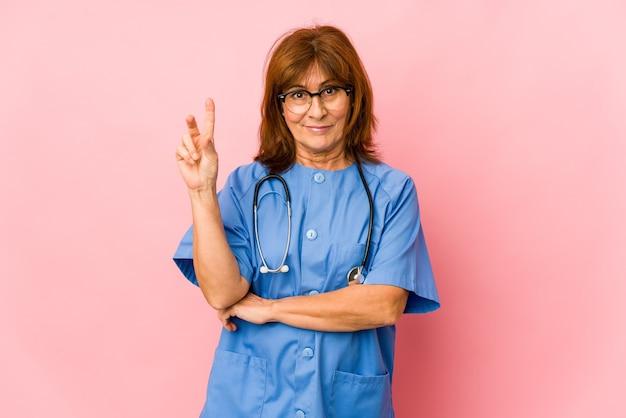Kobieta pielęgniarka kaukaski średnim wieku na białym tle wyświetlono numer dwa palcami.