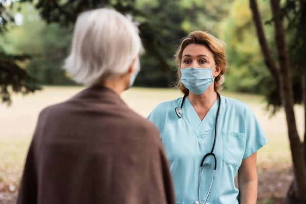 Kobieta pielęgniarka rozmawia na zewnątrz ze starszą kobietą