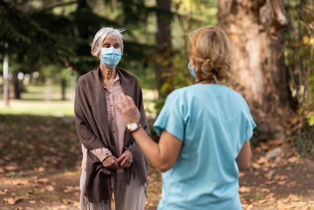 Kobieta pielęgniarka sprawdzanie starszej kobiety na zewnątrz w domu opieki