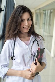 Kobieta pielęgniarka trzymając historię medyczną pacjenta w notatniku i stojąc samotnie w nowoczesnym korytarzu szpitala