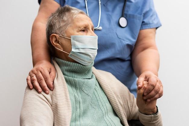Kobieta pielęgniarka trzymając rękę starszej kobiety w domu opieki
