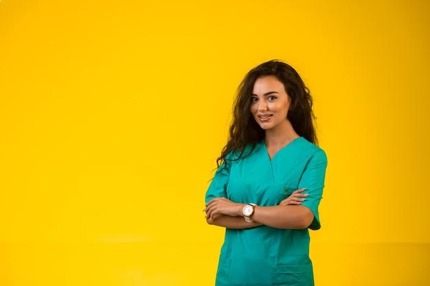 Kobieta pielęgniarka zamykając ręce i uśmiechając się.