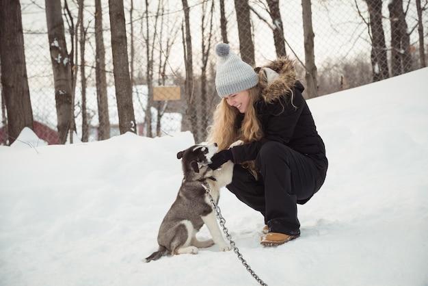 Kobieta pieści młodego psa syberyjskiego