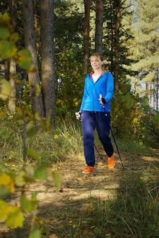 Kobieta piesze wędrówki leśną drogą w słoneczny dzień