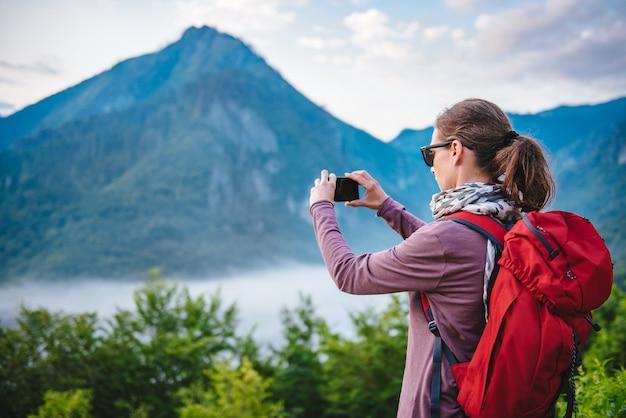 Kobieta, piesze wędrówki w górach i robienie zdjęć za pomocą smartfona