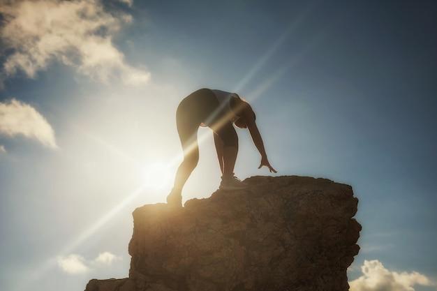 Kobieta piesze wycieczki na szczyt góry o zachodzie słońca