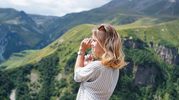 Kobieta piesze wycieczki w góry w czasie słonecznego dnia. widok kazbegi, gruzja. piękne naturalne górskie tło