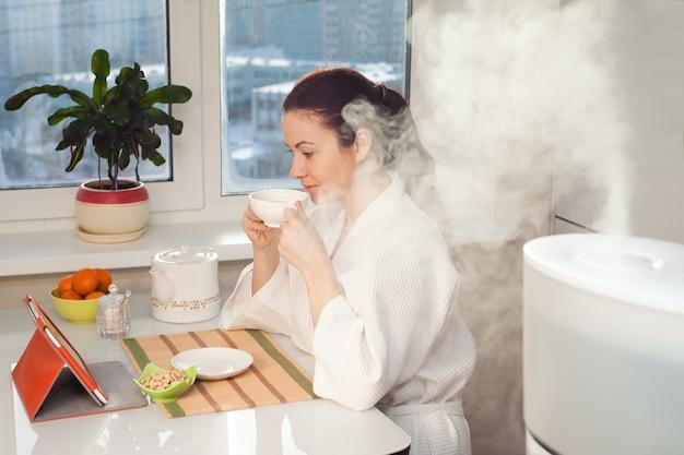 Kobieta pijąca herbatę czytająca tabletkę w pobliżu nawilżacza