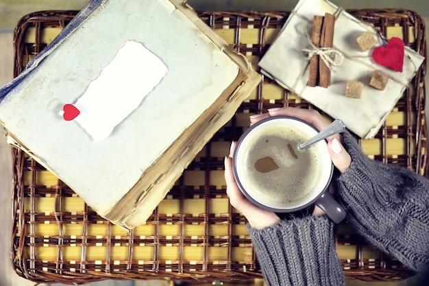 Kobieta pijąca kawę i patrząca na kartkę walentynki