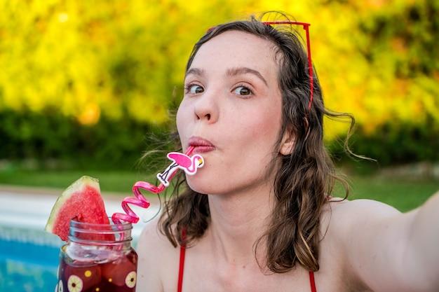 Kobieta pijąca koktajl latem z arbuzem i basenem w tle