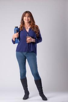 Kobieta pijąca mate trzymająca termo