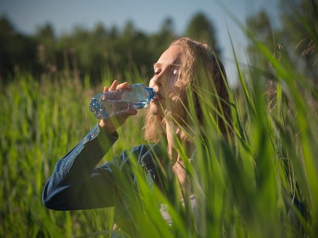 Kobieta pije butelkę woda na gorącym letnim dniu