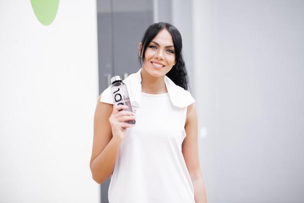 Kobieta pije butelkę wody na siłowni.