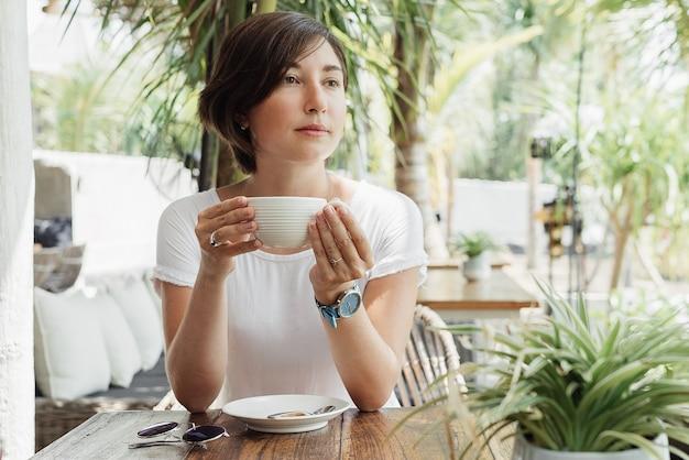 Kobieta pije cappuccino w kawiarni na świeżym powietrzu