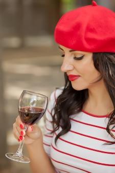 Kobieta pije czerwone wino w plenerowej kawiarni w czerwonej nakrętce