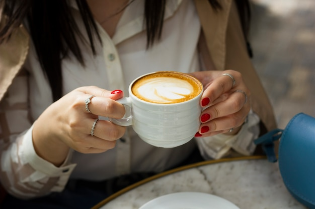 Kobieta pije filiżankę cappuccino