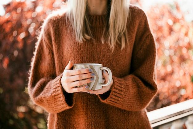 Kobieta pije filiżankę ciepłej pomarańczowej herbaty ziołowej
