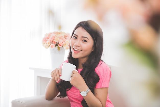 Kobieta pije filiżankę herbaty lub kawy