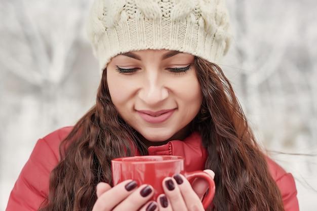 Kobieta pije gorącą herbatę lub kawę z kubka w przytulnym ogrodzie snowy house w zimowy poranek. piękna kobieta cieszy się zimę outdoors z kubkiem ciepły napój. przerwa świąteczna. przytulny zimowy styl życia.