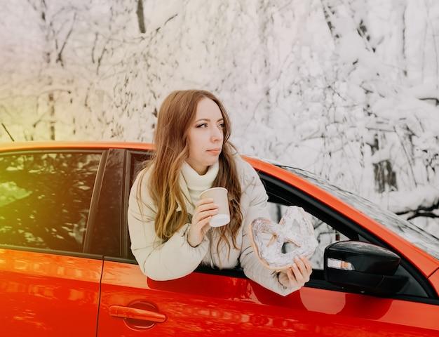 Kobieta pije gorącą kawę i trzyma bułkę w czerwonym samochodzie w zimowym lesie. światło słoneczne.