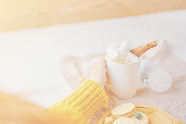 Kobieta pije gorącą kawę z marshmallows i cynamonem w żółtym pulowerze