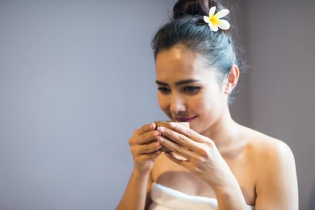 Kobieta pije gorącą zieloną herbatę w spa