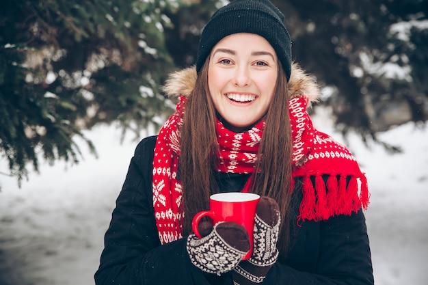 Kobieta pije gorącej herbaty w zima lesie