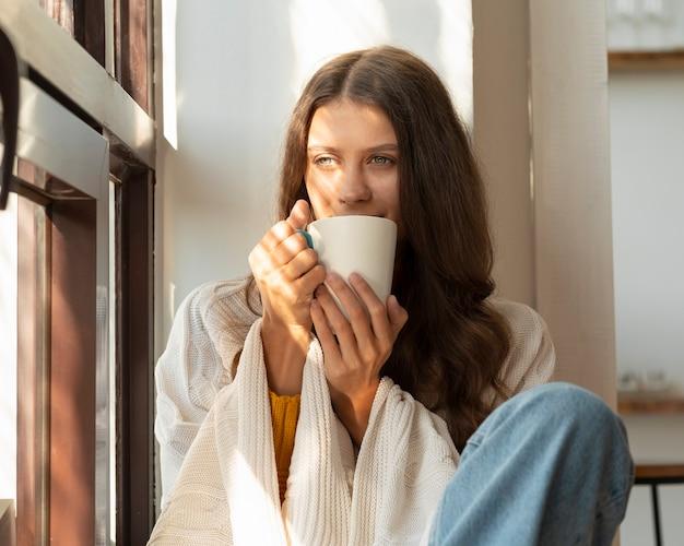 Kobieta pije gorący napój i ciesząc się rano, siedząc w oknie i marzy