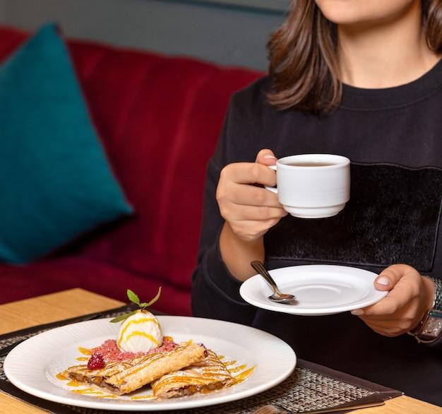 Kobieta pije herbatę z deserem w restauracji