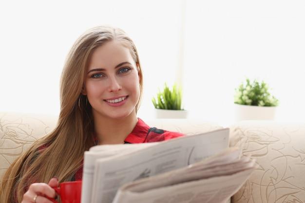 Kobieta pije kawę i czytanie siedzi na kanapie