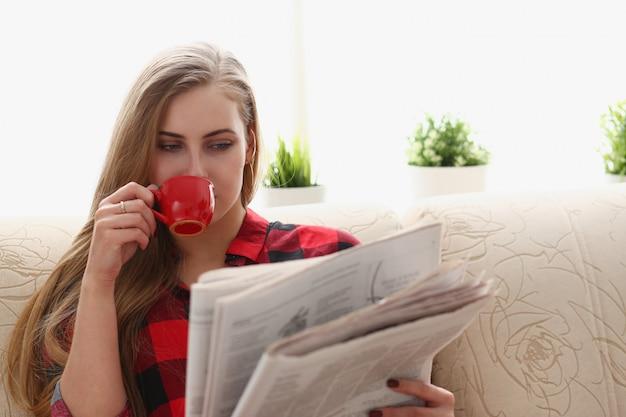Kobieta pije kawę i czytanie siedzieć na kanapie