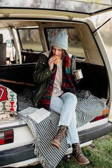 Kobieta pije kawę i je rogalika w furgonetce