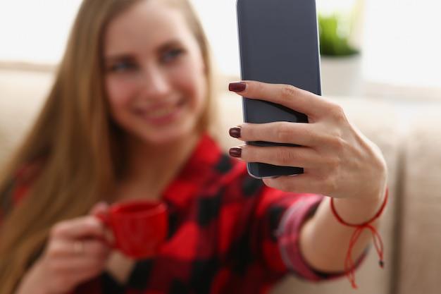Kobieta pije kawę i patrzeje laptop