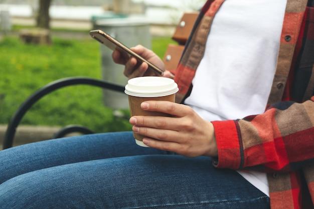 Kobieta pije kawę i używa smartfona w parku. przerwa na lunch
