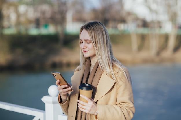 Kobieta pije kawę i używa smartfona