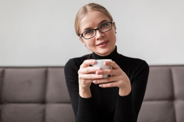 Kobieta pije kawę na kanapie