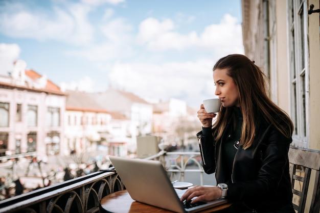Kobieta pije kawę na tarasie wihle pracuje na laptopie.