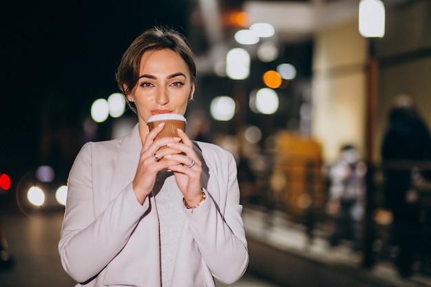 Kobieta pije kawę outside w ulicie przy nocą