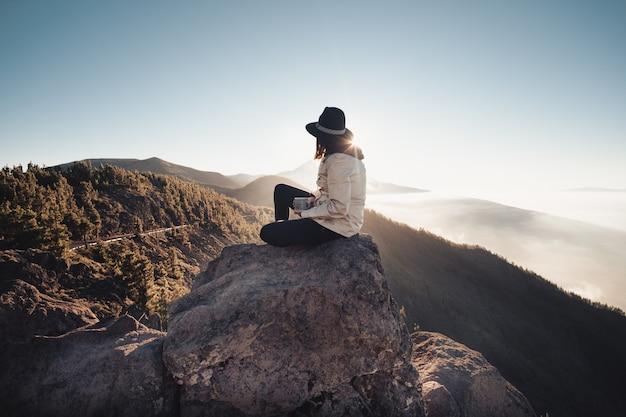 Kobieta pije kawę podczas oglądania przyrody