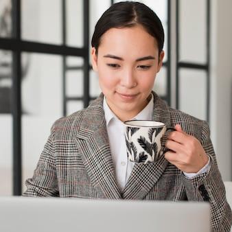 Kobieta pije kawę podczas pracy