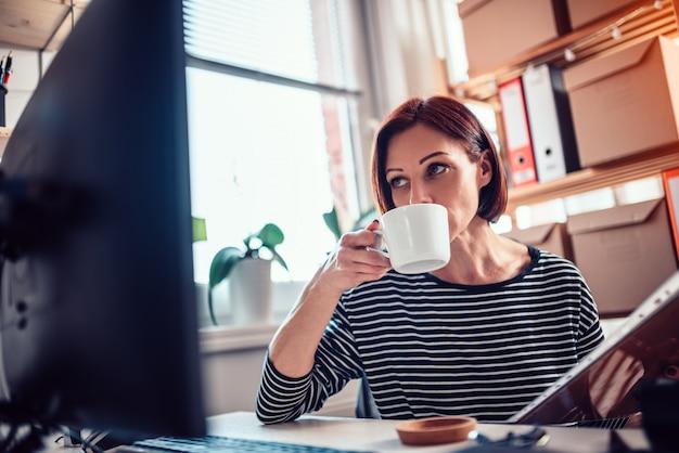 Kobieta pije kawę przy biurem