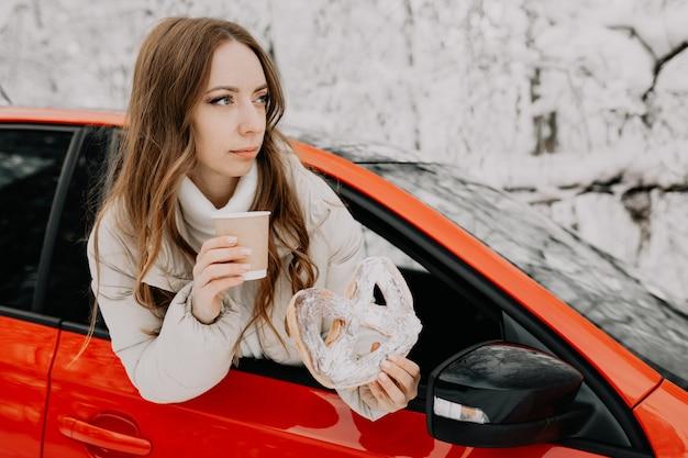 Kobieta pije kawę w czerwonym samochodzie w zimowym lesie