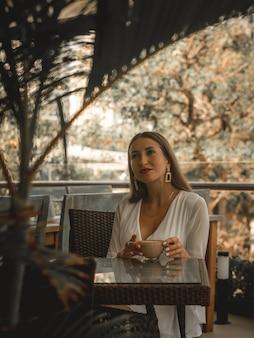 Kobieta pije kawę w kawiarni. beżowa edycja blogów