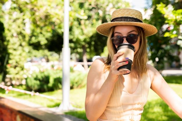 Kobieta pije kawę z kapeluszem